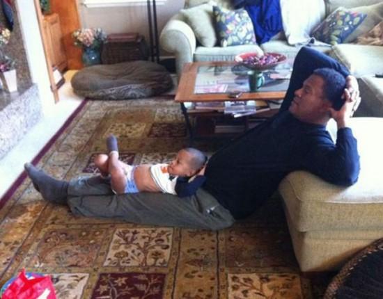 膝の上で父親と同じポーズをとる子供